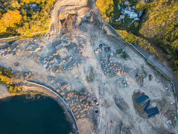 the top view of the construction site at the initial stage of construction and preparation of the ground with a drilling rig, excavators and three trucks awaiting loading of soil for transportation - land vehicle stock photos and pictures