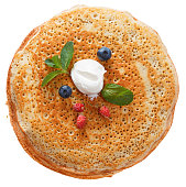 The top view on pancakes with holes. Made of yeast dough. Decorated with sour cream, mint and fresh