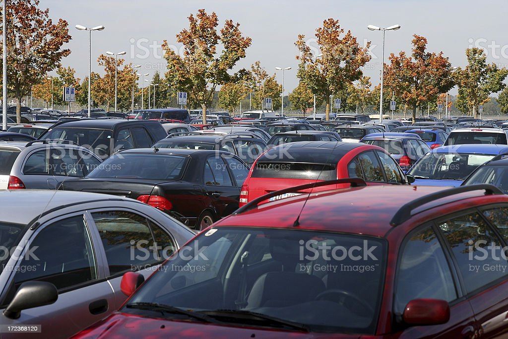 The tops of many rows of cars in a parking lot with trees stock photo