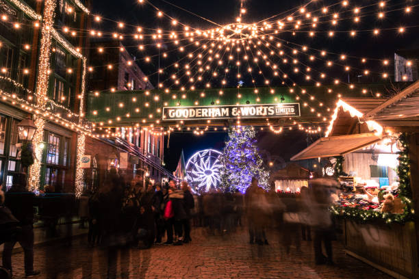 The Toronto Christmas Market at the Distillery District. Lights hanging over the street in front of the Gooderham & Worts sign.