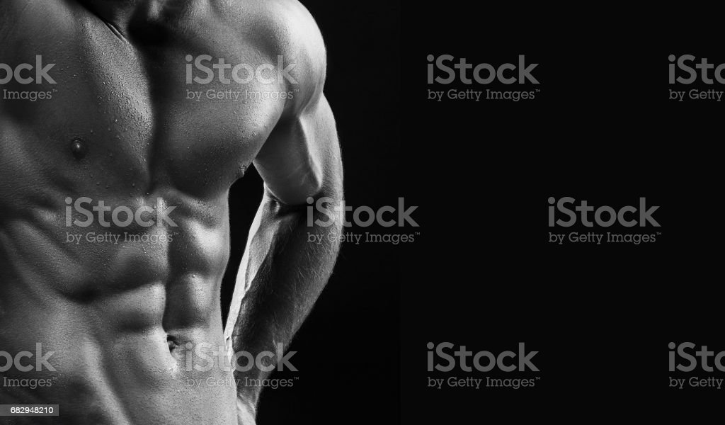 The torso of attractive male body builder on black background royalty-free stock photo
