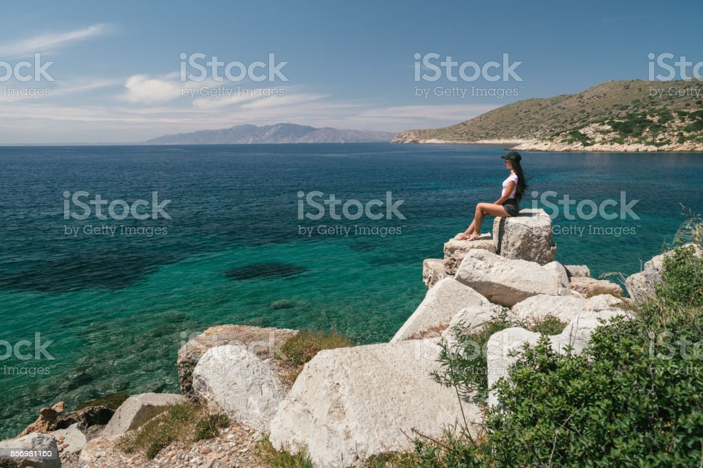 The tourist admires the sea view. The girl is on vacation. A woman stands on the edge of a cliff and is very happy. stock photo