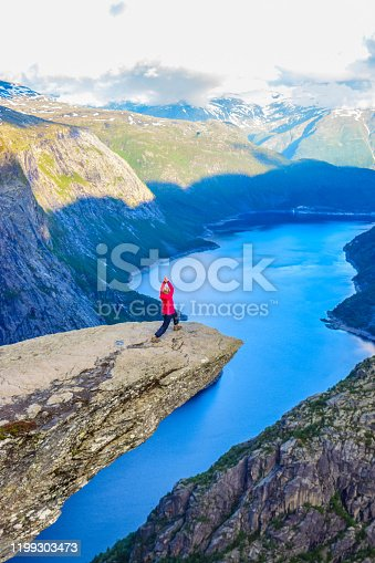 The girl stands in the warrior poses on the Trolltunga, Norway.