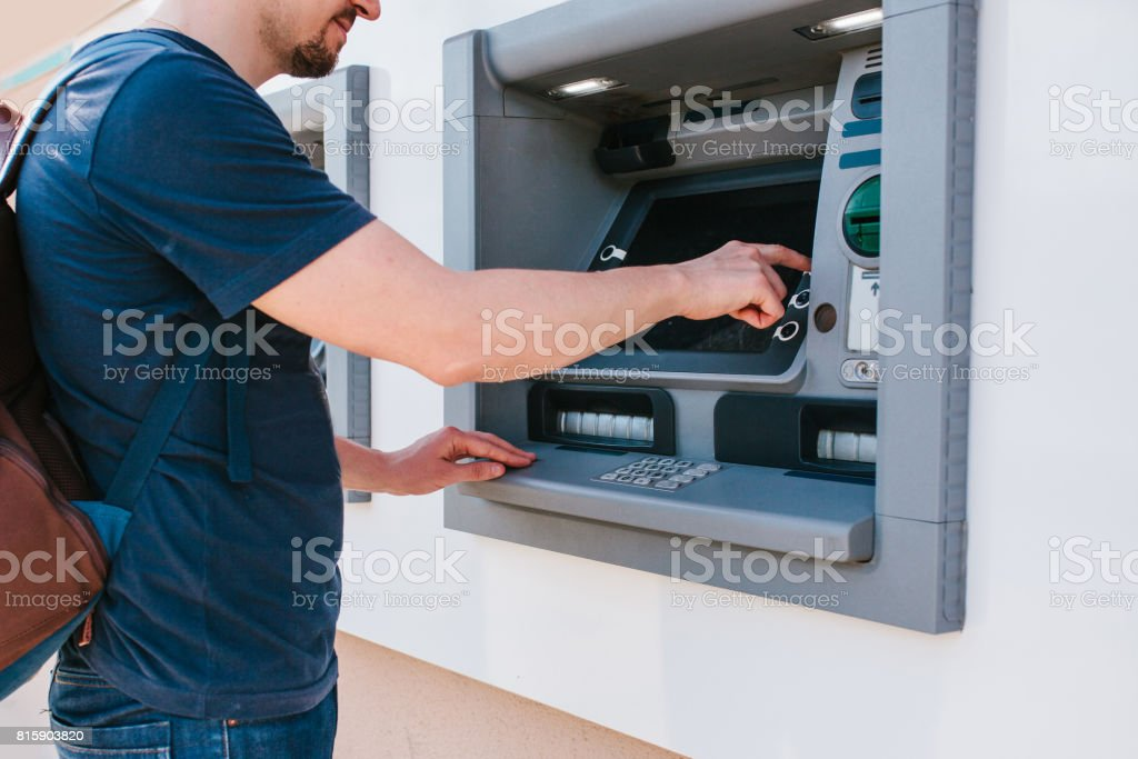 The tourist withdraws money from the ATM for further travel. Finance, credit card, withdrawal of money. Life style. Journey. Vacation. stock photo