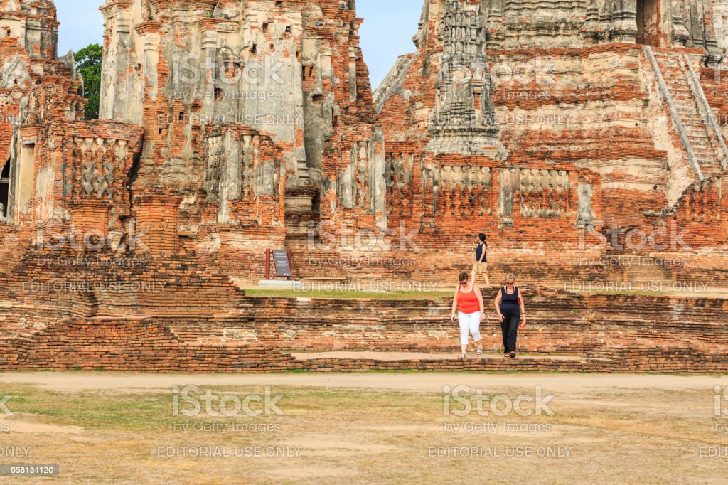 AYUTTHAYA,  THAILAND - MARCH 25, 2017 : The tourists  visiting ruin brick temple of Wat Chaiwattanaram  in Ayutthaya Historical Park, Thailand. stock photo