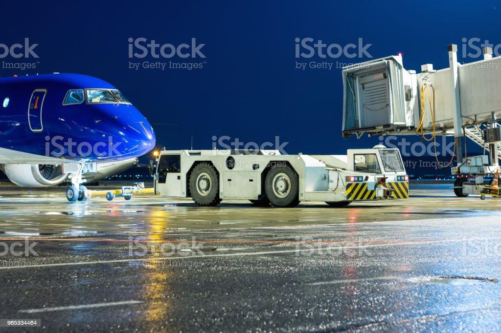 견인 트랙터 밤 공항 앞치마에 공기 다리에서 여객 비행기를 다시 롤 - 로열티 프리 게이트 스톡 사진