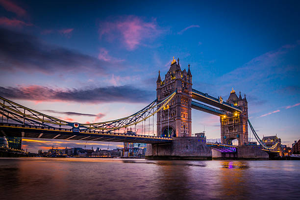 The Tower Bridge of London at dusk A vivid and spectacular view in twilight from the river Thames Southbank overlooking the iconic landmark and famous tourist attraction's night illumination of Tower Bridge in the capital city of London, United Kingdom. Shot with Canon EOS 60D, ISO 100, boosted saturation to emphasize colours, slight vignette added bascule bridge stock pictures, royalty-free photos & images