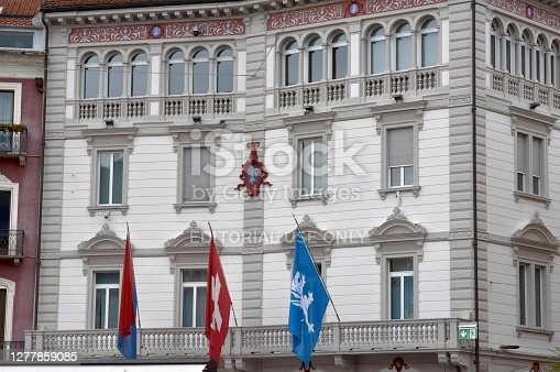 Locarno / Switzerland - September 26 2020: The Town Hall of Locarno is located in an ancient Palace called Palazzo Marcacci in Italian. The building has three flags on the facade, a Swiss one, one of canton Ticino and one of the town Locarno.