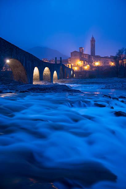la città di bobbio con un ponte al blue ore - bobbio foto e immagini stock