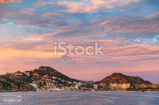 A view of the town of Cabo San Lucas at sunset taken from a ship just out from the shoreline