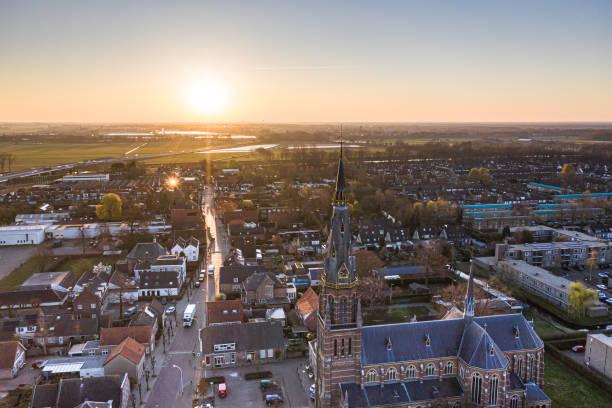 a cidade vista de cima durante o nascer do sol em waalwijk, noord brabant, países baixos - sol nascente horizonte drone cidade - fotografias e filmes do acervo