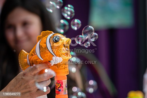 New York, USA - June 22, 2019: the toy seller is demonstrating to the buyers a soap bubble gun