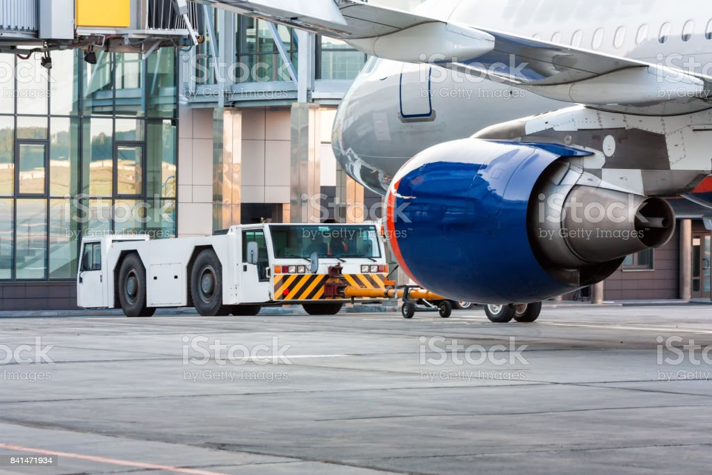 The tractor is towing the passenger airplane стоковое фото
