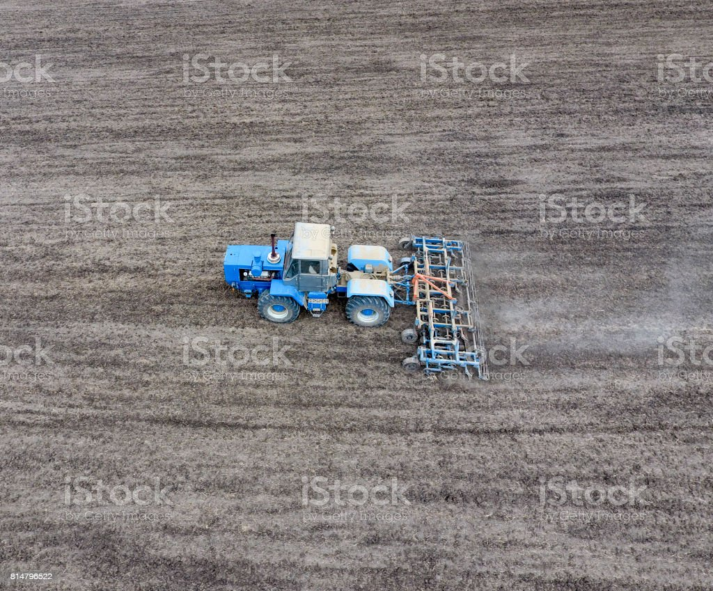 The tractor plows the field. Under sowing, the soil is loosened on the field. stock photo