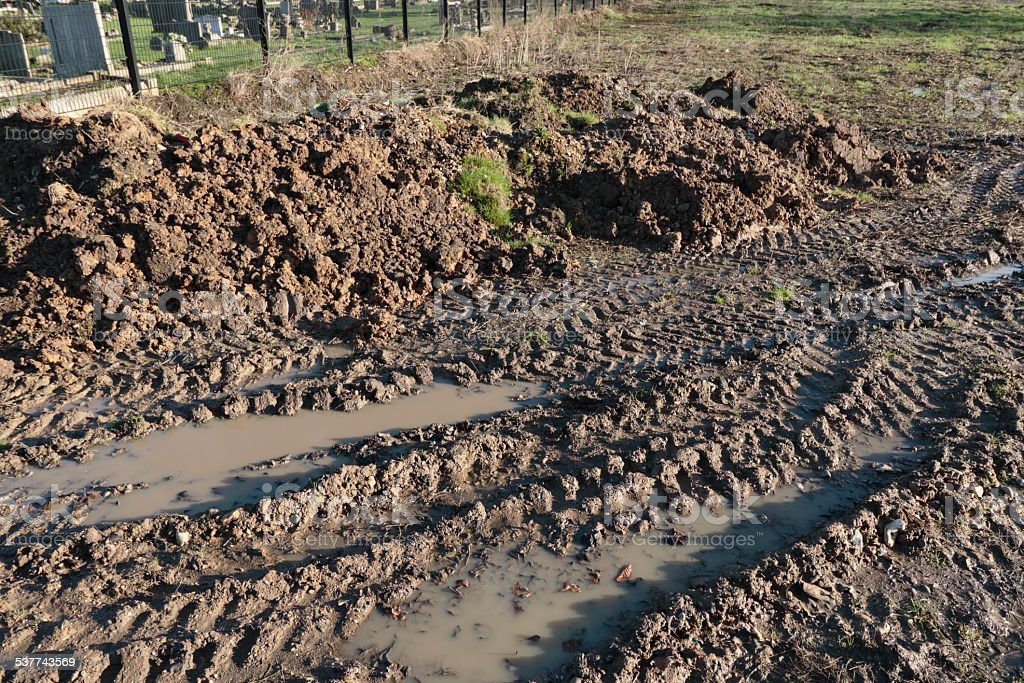 Muddy puddle tyre marks left by building site vehicle stock photo
