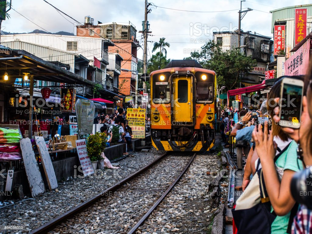 The tradition train is passing through the middle of the shopping area where it is so crowded of the tourists. Anyway, people are love to sell it. stock photo