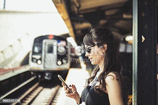 Women on subway station using mobile phone
