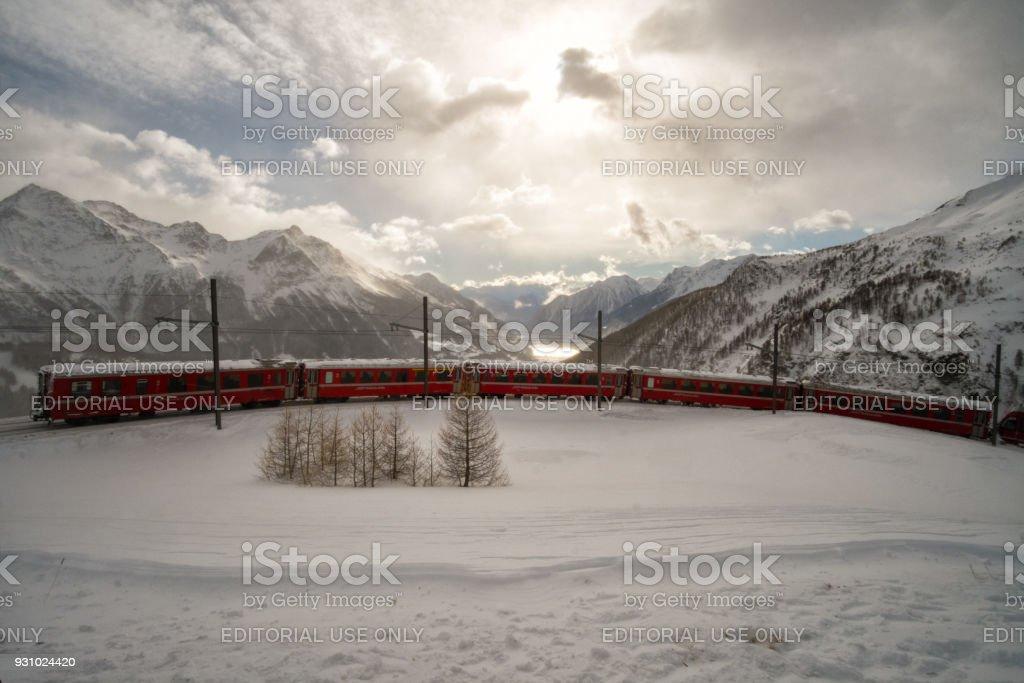 The train Bernina Express descends towards the lake stock photo
