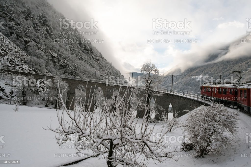 The train Bernina Express is passing over the Brusio spiral viaduct stock photo