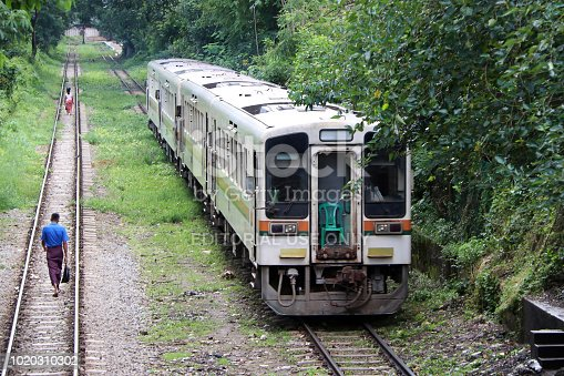 Yangon, Myanmar, 6 June 2018: The train is running on the track. behind of Myanmarese villager walking on the parallel railroad track.
