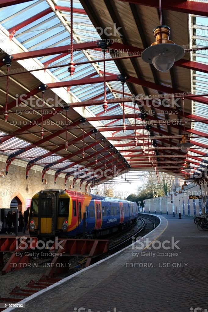 The train shed of Windsor & Eton Riverside Station in Windsor, England, with its two platforms, a train waiting to depart, and red buffers stock photo