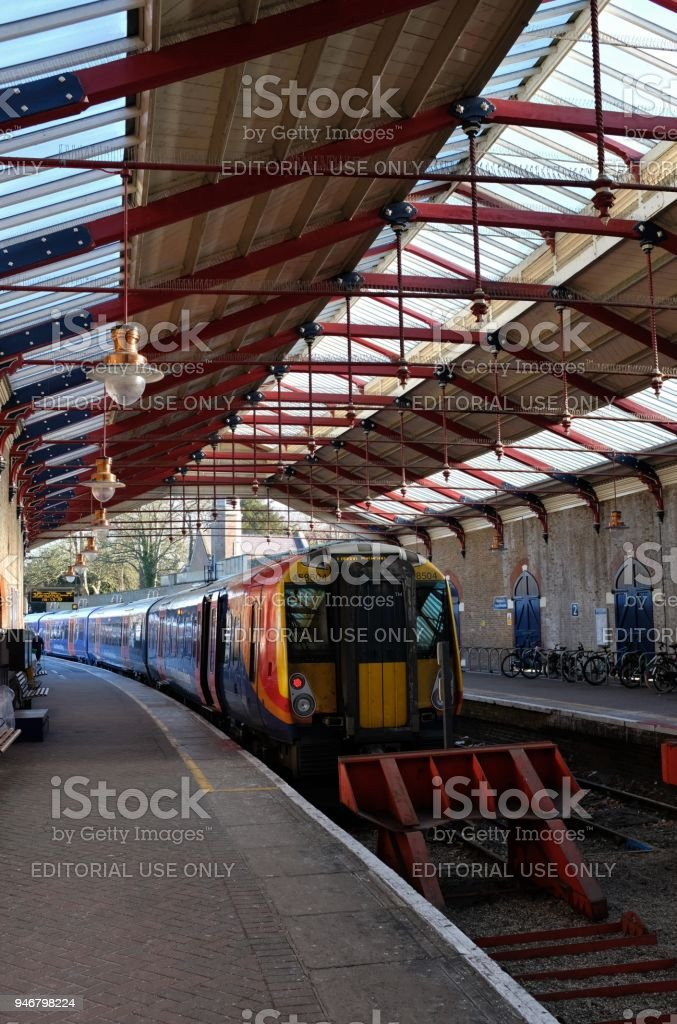 The train shed of Windsor & Eton Riverside Station in Windsor, England, with its two platforms, a train waiting to depart, red buffers, and commuters' bicycles stock photo