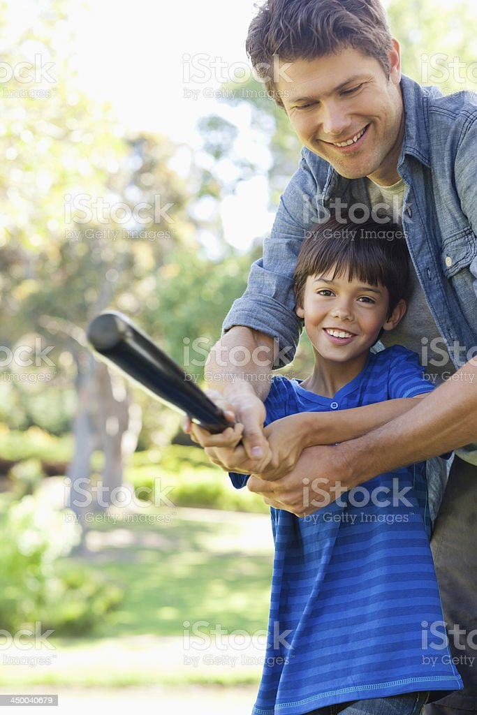 The training son and dad smile while swinging stock photo