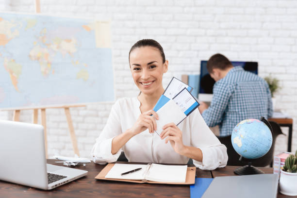 The travel agent keeps tickets for the plane in the travel agency. stock photo