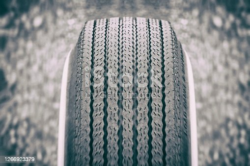 The tread pattern of an old-fashioned car tire. the blurred asphalt can be seen in the background