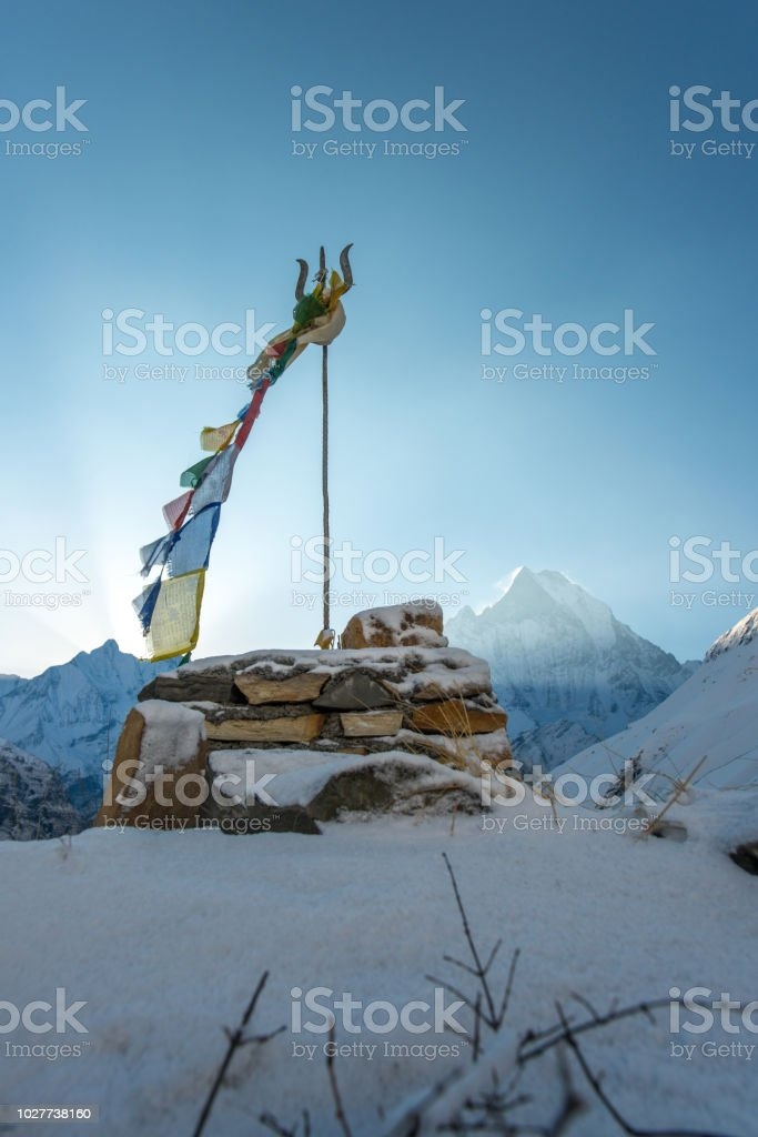 The trident of Shiva the god of destruction in Hinduism with the beautiful Machapuchare mountain (Mt.Fish tail) the holy mountain in Himalayas mountains range of Nepal at sunrise. stock photo