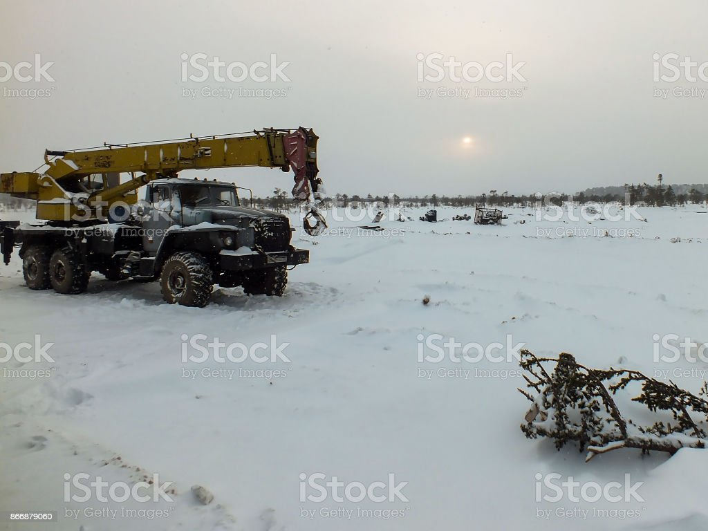 The truck crane in the snow in the field. stock photo