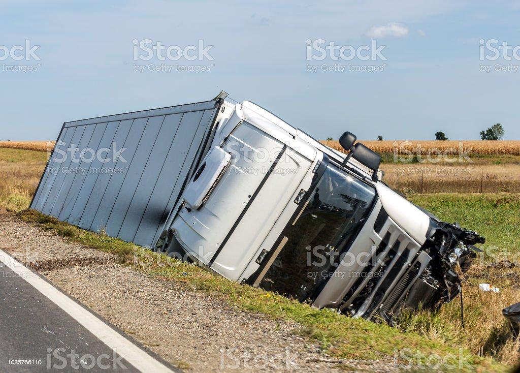 El carro se encuentra en una zanja de lado después del accidente de carretera. - Foto de stock de Accidente de automóvil libre de derechos