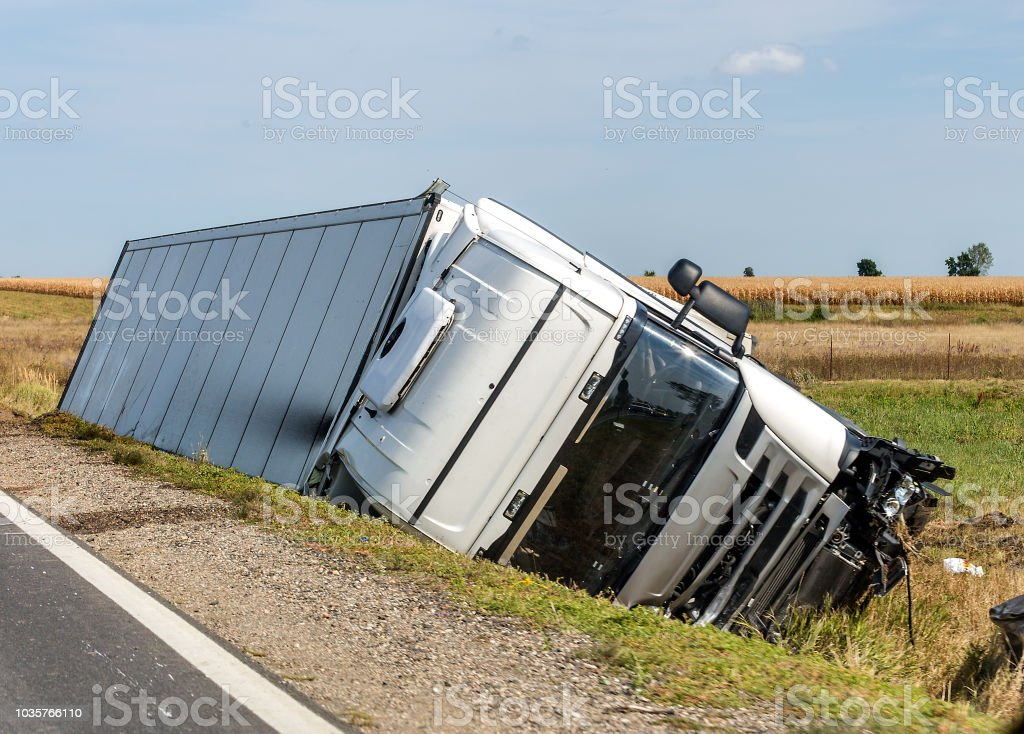 The truck lies in a side ditch after the road accident. – zdjęcie