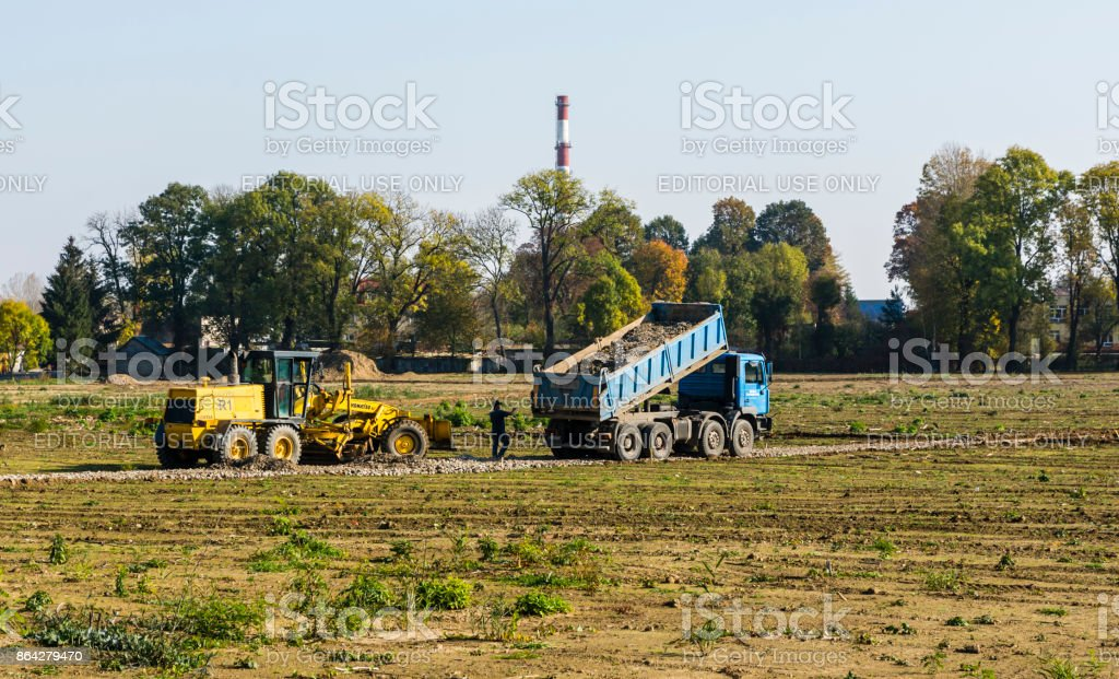 The truck pours the aggregate into the road foundation. The grader will match them. royalty-free stock photo