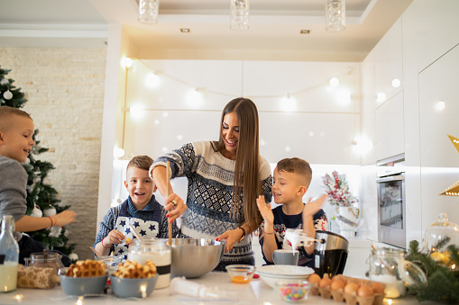 Mother with three sons making Christmas sweets