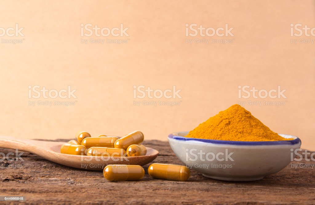 The Turmeric Powder Capsule And Roots Curcumin On Wooden