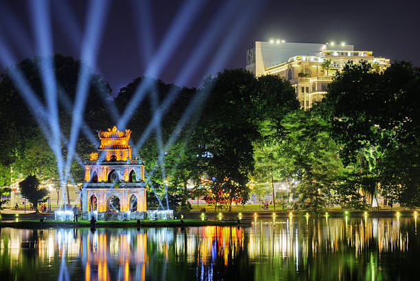 The Turtle Tower on the Hoan Kiem Lake. Hanoi Night view of the Hoan Kiem Lake (Lake of the Returned Sword) and the Turtle Tower among blue light rays at historic centre of Hanoi in Vietnam. The Hoan Kiem Lake is a popular tourist destination. hanoi stock pictures, royalty-free photos & images