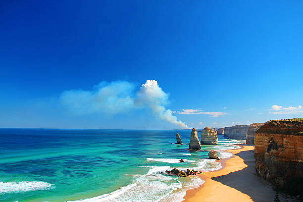 the twelve apostles, australia, and a bushfire - bush stockfoto's en -beelden