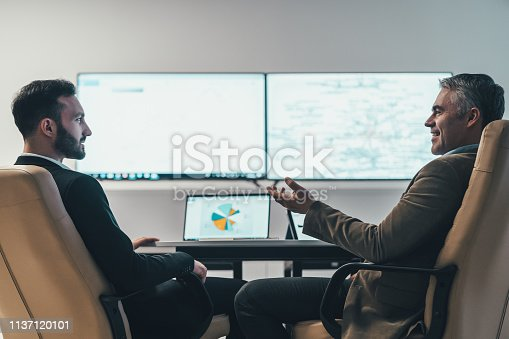 The two businessmen discussing at the table near a screen
