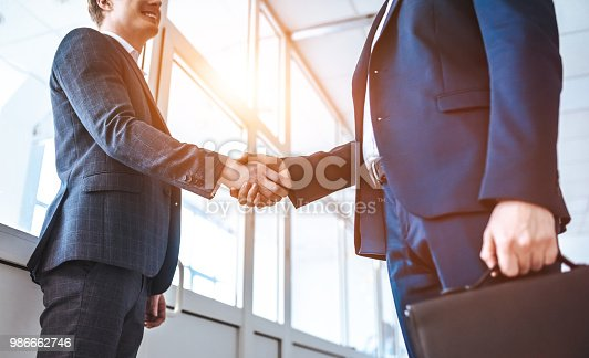 istock The two businessmen greeting in the office hall 986662746