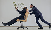 The two businessmen playing with chair and throwing money