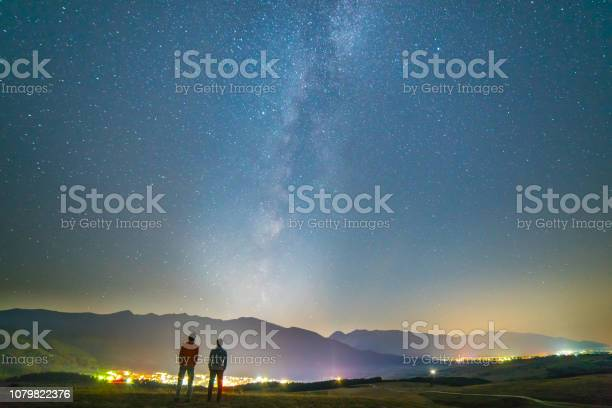 Photo of The two friends stand on the background of the stars. night time