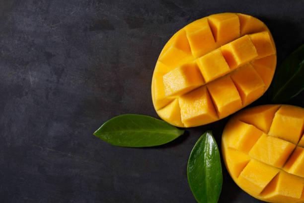las dos mitades de mango maduro en la mesa texturada negro. vista desde arriba. copia espacio. - mango fotografías e imágenes de stock
