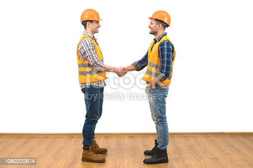 istock The two happy engineers handshake on the white wall background 1060202614
