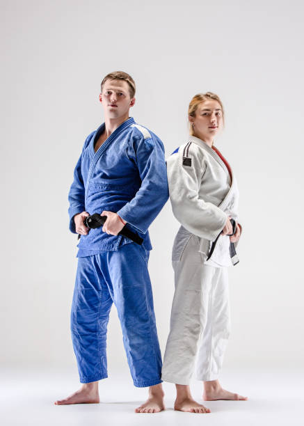 The two judokas fighters posing on gray - foto de stock