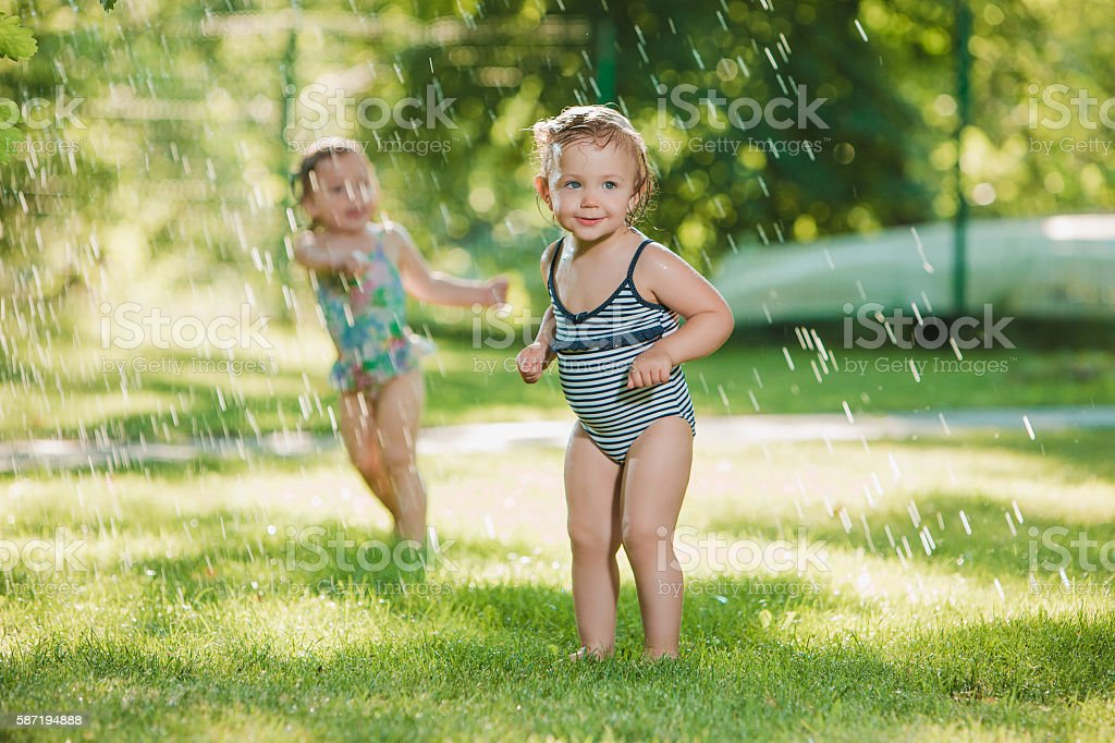 The two little baby girls playing with garden sprinkler. stock photo