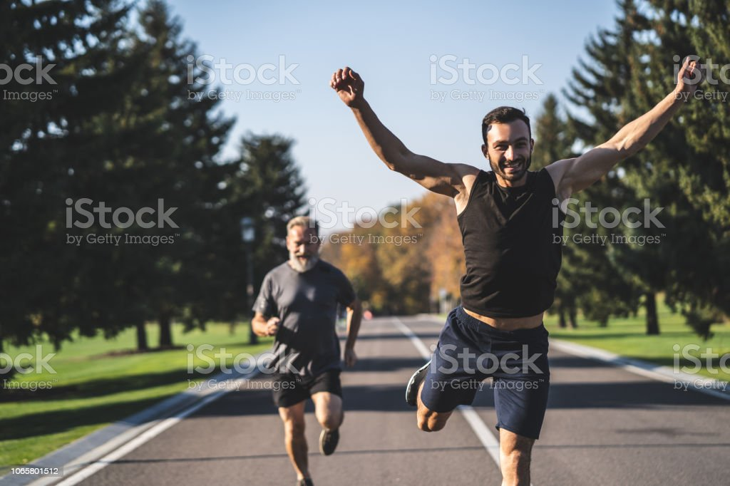 The two men running on the road in the park