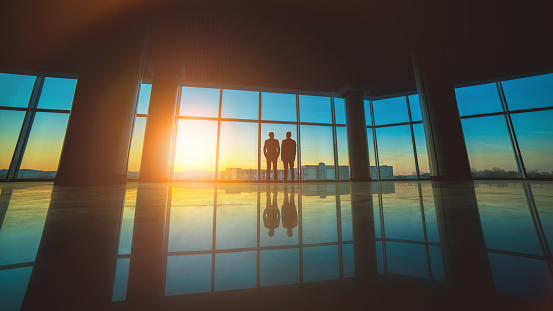 The two men stand near the panoramic window on the sunset background