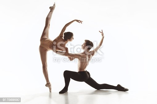 The two young modern ballet dancers dacing or posing over gray studio background. The choreography and contemporary concept