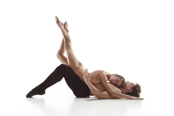die beiden jungen modernen balletttänzer posieren über graue studio-hintergrund - männliche körperkunst stock-fotos und bilder